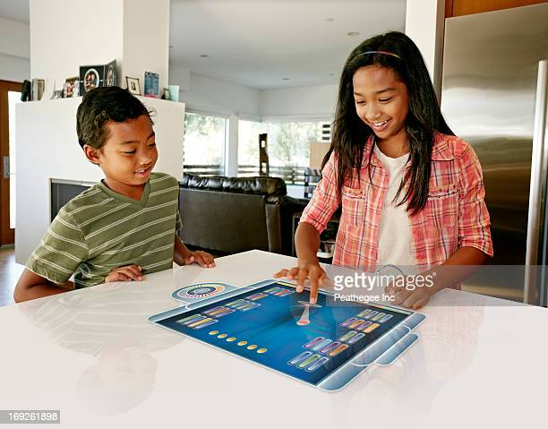 Children playing on computer in table