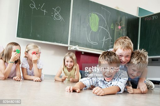 Children playing on floor in classroom : Stock Photo