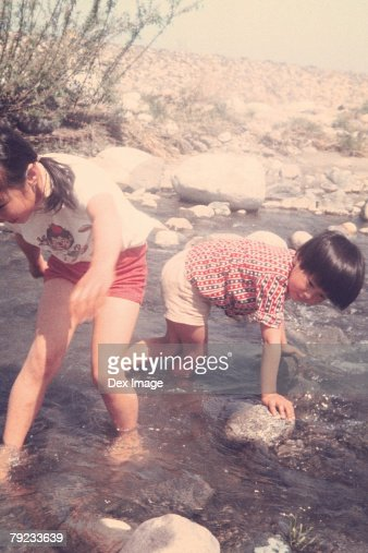 Children playing on riverbank : Stock Photo