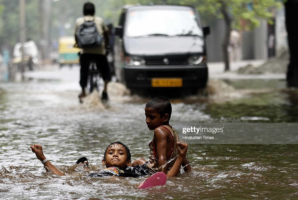 Children playing on the water logged road after the heavy rainfall at Andrews Gunj on June 17, 2013 in New Delhi, India. The Delhi government began evacuating people from low-lying areas along the banks of the Yamuna river after 8.06 lac cusecs of water was released from Hathnikund barrage in Haryana.