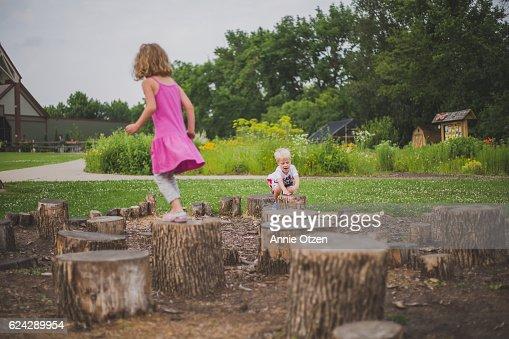 Children Playing on Tree Stumps