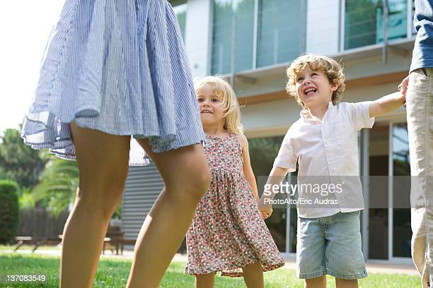 Children playing outdoors with their parents
