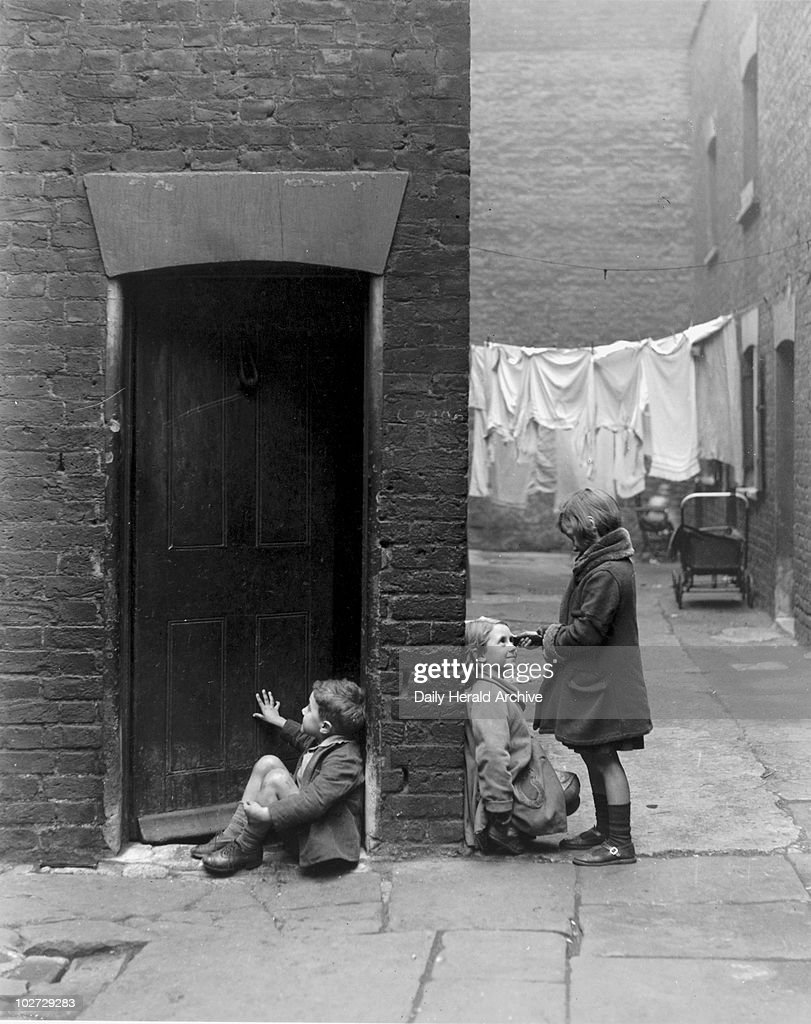 Children playing outside their slum home in Southwark, 16 December 1932. Children playing outside their slum home in Southwark, London, on the 16 December 1932. Photograph by James Jarche.