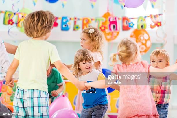 Enfants jouant anneau autour du Rose de fête d'anniversaire.