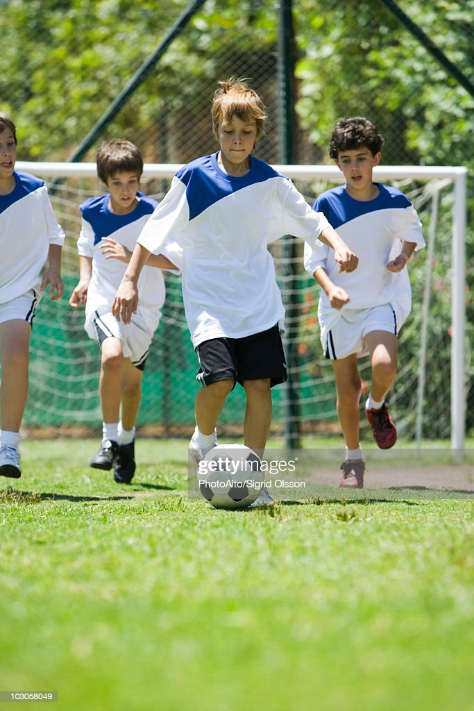Children playing soccer, cropped : Stock Photo