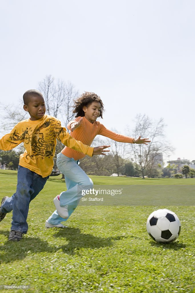 Children (7-10) playing soccer in park : Stock Photo