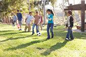 Niños (9 a 14) jugando al fútbol en el parque