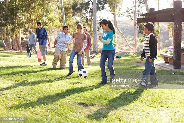 Kinder (9-14) spielen Fußball im park