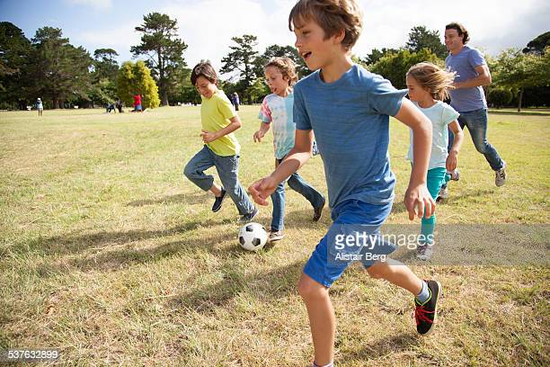 Children playing soccer in park