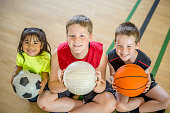 A multi-ethnic group of elementary age children are at summer day camp, sitting on the gymnasium floor, holding balls in their lap. They are smiling and looking at the camera.