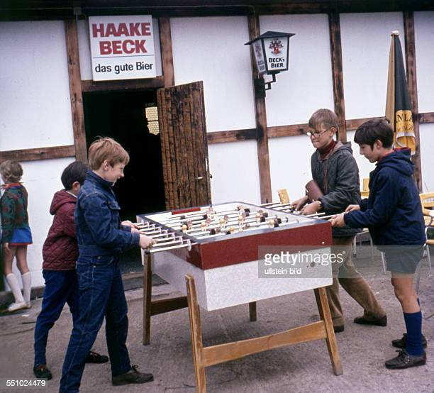 Children playing table football in front of a restaurant 1960ies
