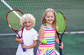 Boy and girl playing tennis on outdoor court. Kids with tennis racket and ball in sport club. Active exercise. Summer activities for children. Training for young kid. Child learning to play.
