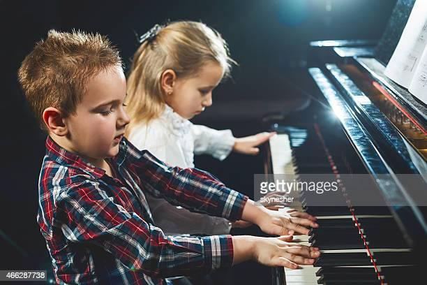 Children playing the piano.