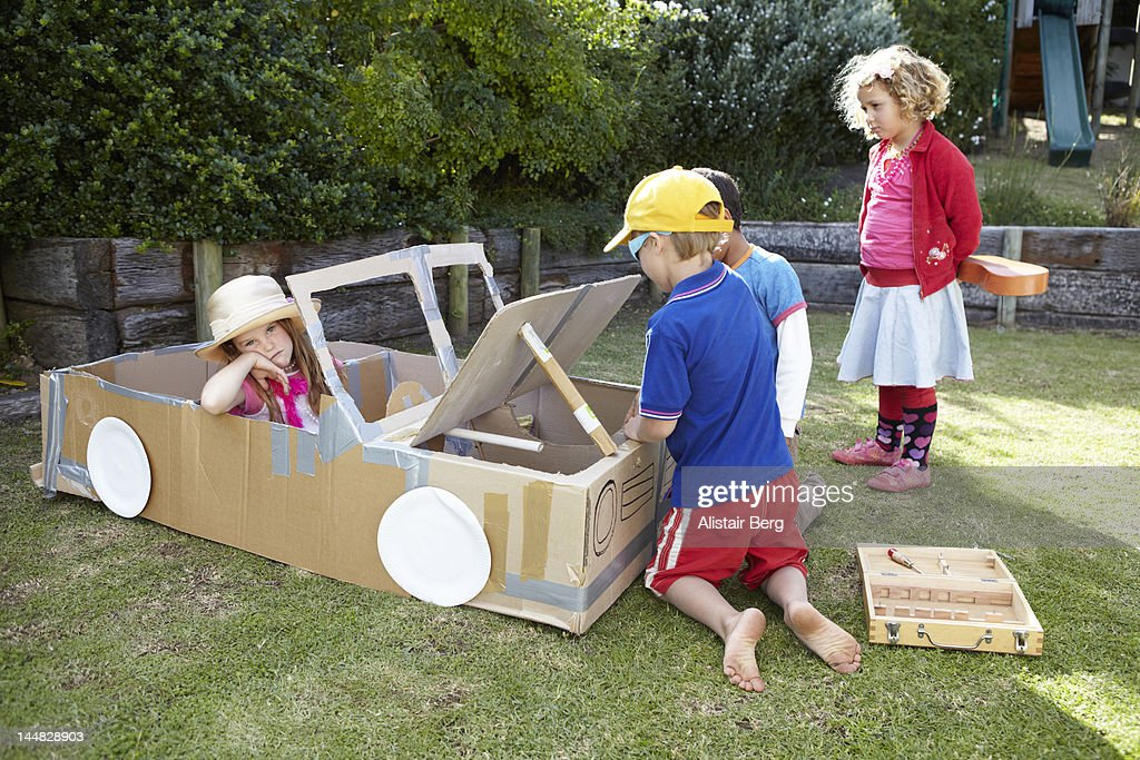 Children playing together with a cardboard car : Stock Photo