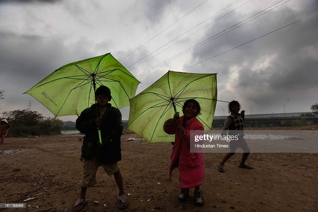 Children playing under overcast sky near ITO Yamuna bridge, on February 16, 2013 in New Delhi, India. The National capital witnessed a total of 18.6 mm of rains since yesterday and the weather is likely to remain cloudy for another day.