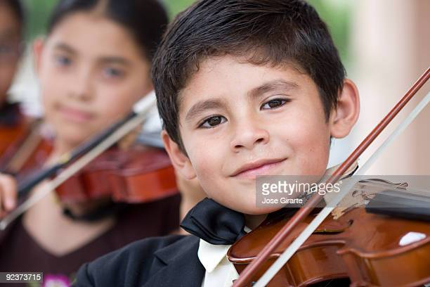 Children playing violins in a classical music concert