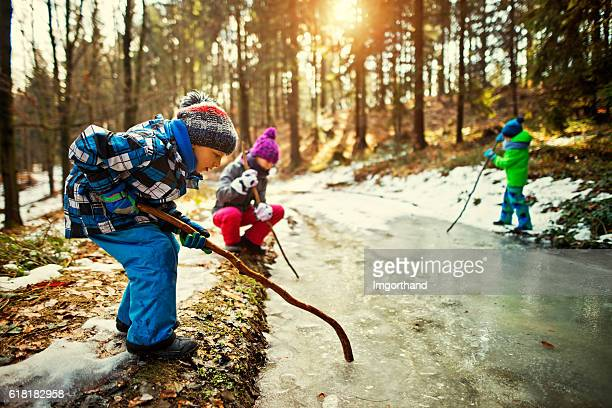 Children playing with a frozen puddle in winter
