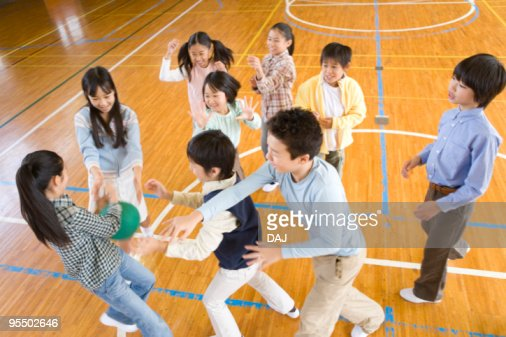 Children playing with ball in gym, blurred motion : Stock-Foto
