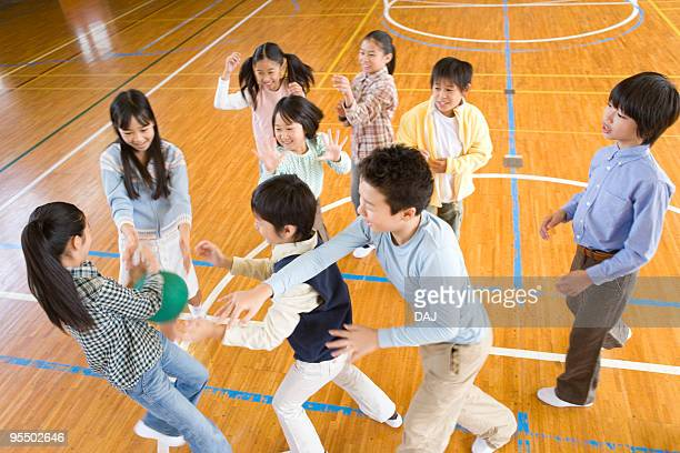 Children playing with ball in gym, blurred motion