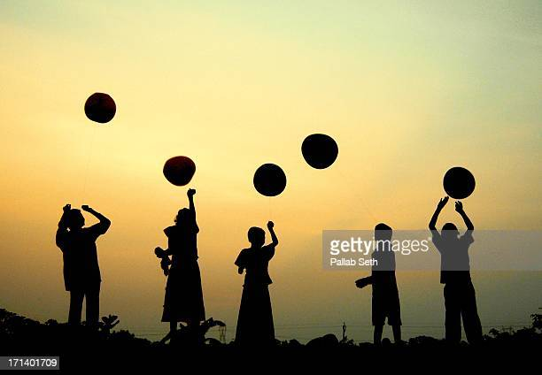 Children playing with balloons at sunset