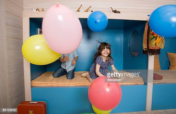 Children (6-9) playing with balloons in bed room, smiling