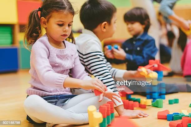 Kinder spielen mit Blöcke auf bereits im kindergarten.