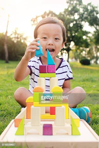 Children playing with blocks in the grass