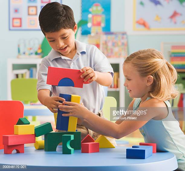 Children (4-7) playing with building block, smiling