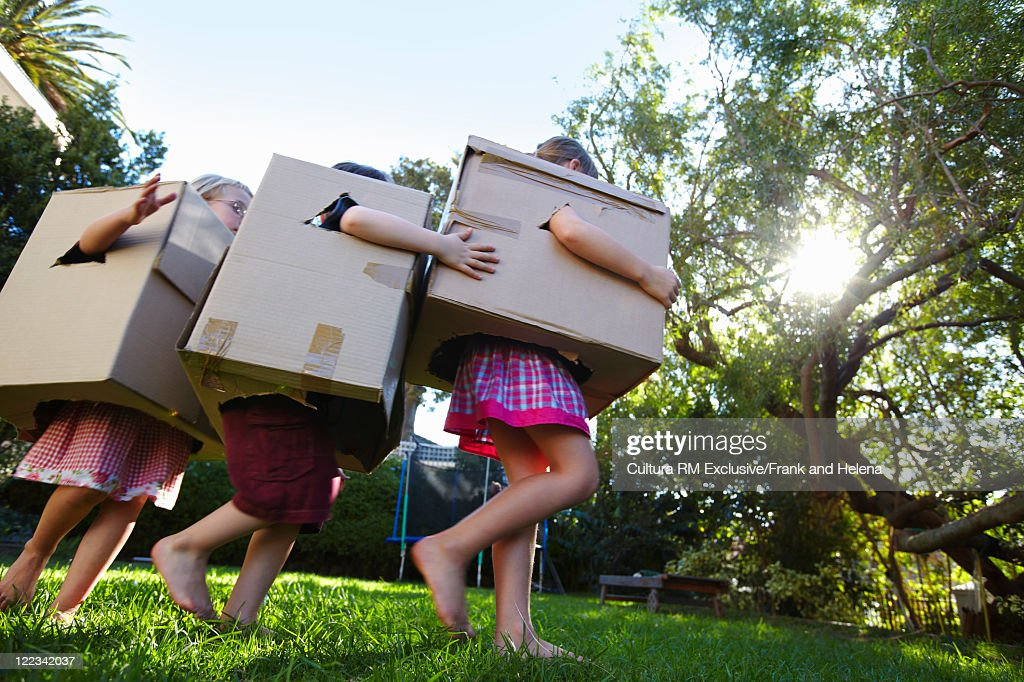 Children playing with cardboard boxes : Stock Photo
