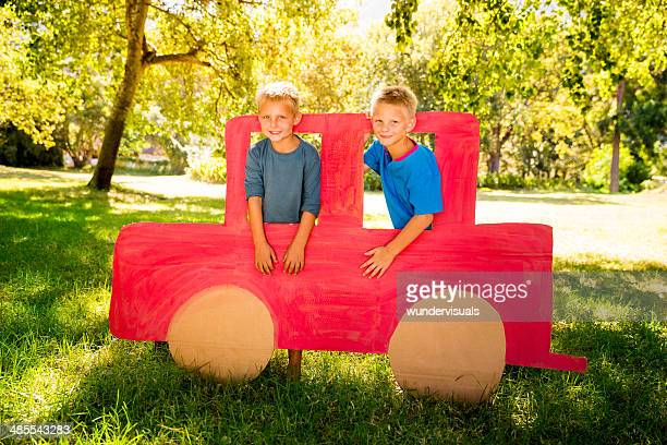 Children playing with cardboard car