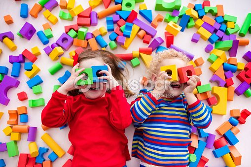Children playing with colorful blocks building a block tower : Stock Photo