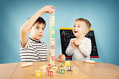 Children playing with cubes on the table. Boys studying letters
