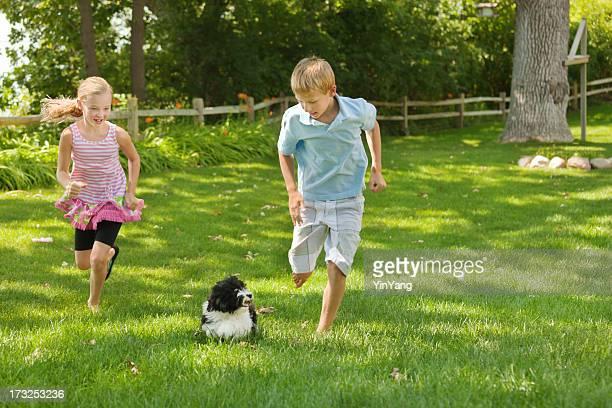 Bambini che giocano con la famiglia animali domestici cane sul prato di erba