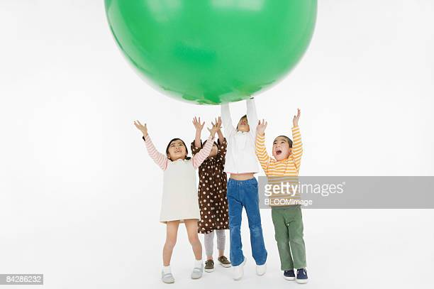 Children playing with large green ball, studio shot