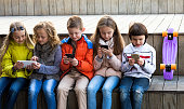 Outdoor portrait of cheerful girls and boys playing with phones