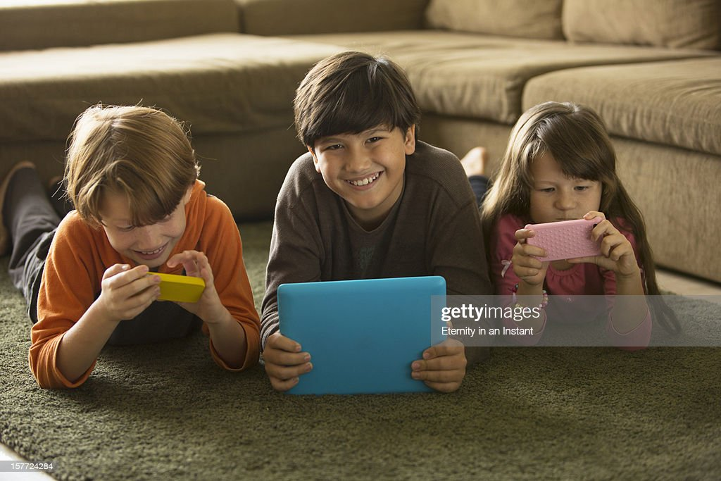 Children playing with phone and digital tablet : Stock Photo