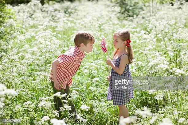 Enfants jouant avec un moulin à vent avec champ de fleurs