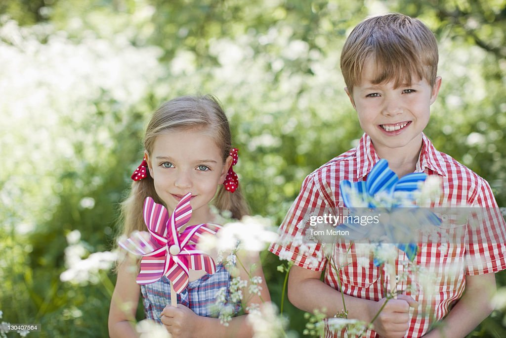 Children playing with pinwheels in park : Stock Photo