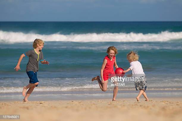 Children playing with red ball on beach