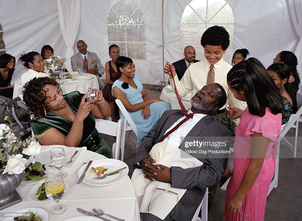 Children (8-12) playing with sleeping mature man at party : Stock Photo