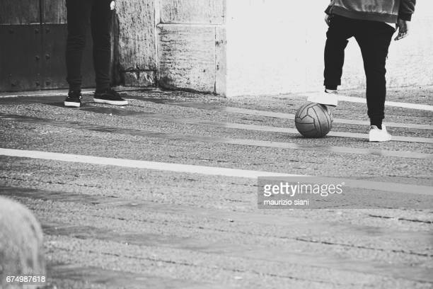 Children playing with soccer ball on urban street