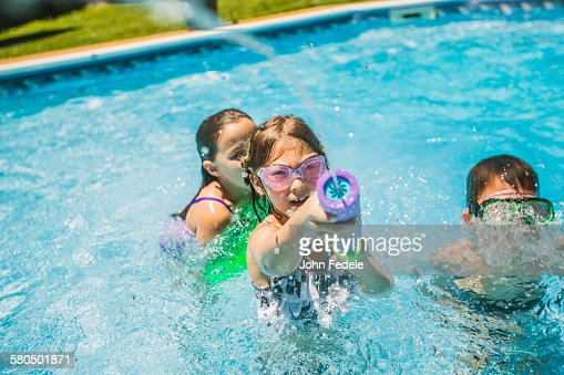children playing with squirt gun in swimming pool stock foto getty images. Black Bedroom Furniture Sets. Home Design Ideas