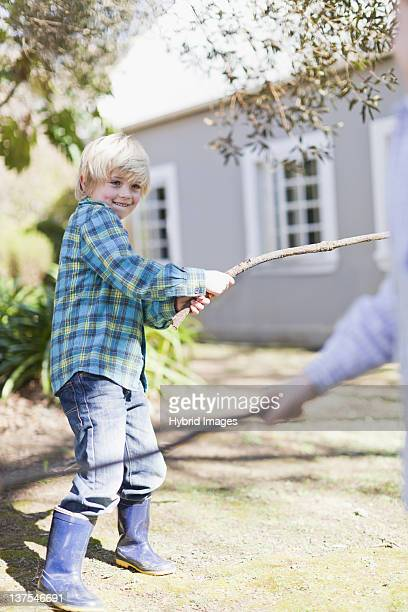 Children playing with sticks outdoors