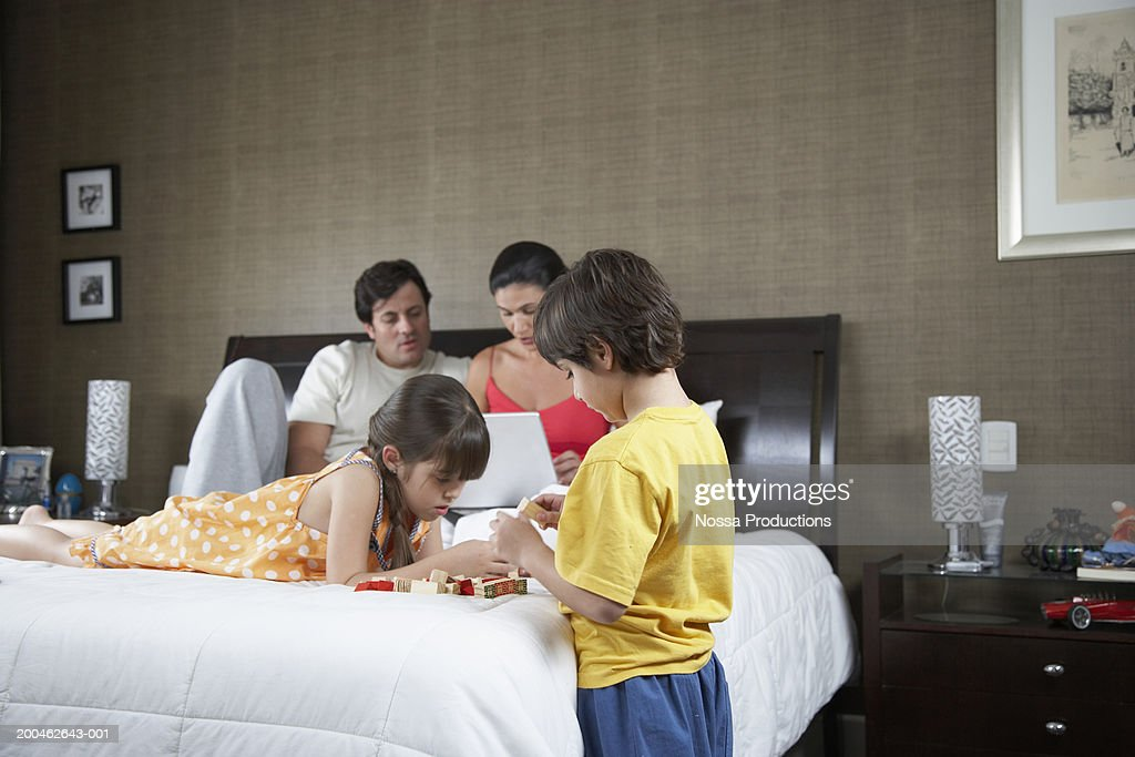 Children (4-10) playing with toys, parents with laptop in background : Stock Photo