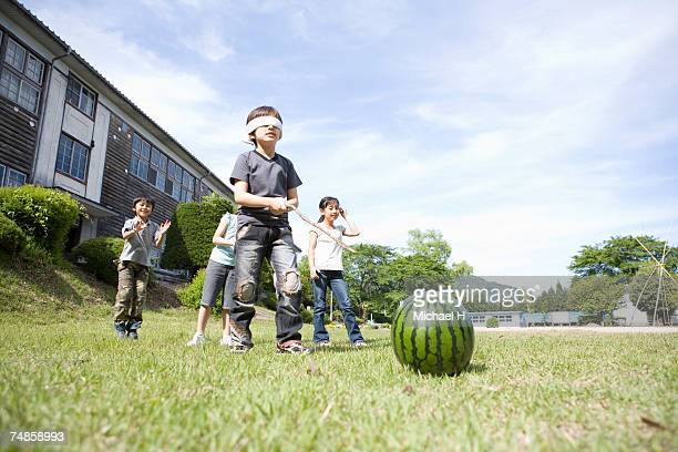 Children (5-7) playing with watermelon outside school