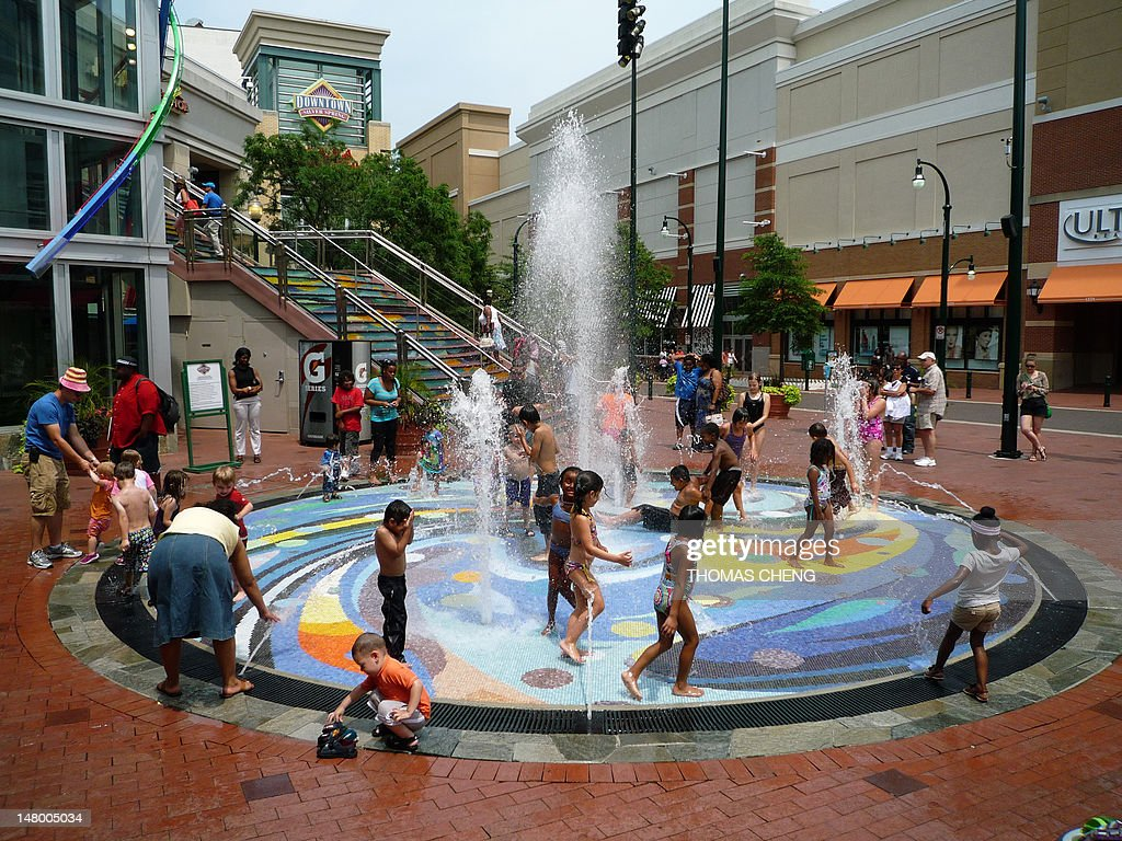 Children plays in a fountain in Silver Spring Maryland north of Washington DC on July 7 2012 as temperatures soar above 100 degrees Fahrenheit and...