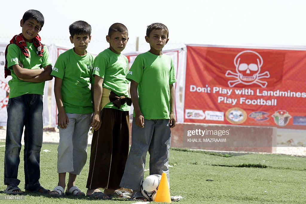 Children pose as they play football at the northern Jordanian Zaatari refugee camp on July 6, 2013 in Mafraq near the border with Syria. At background, the banner reads 'Don't play with landmines, play football'.