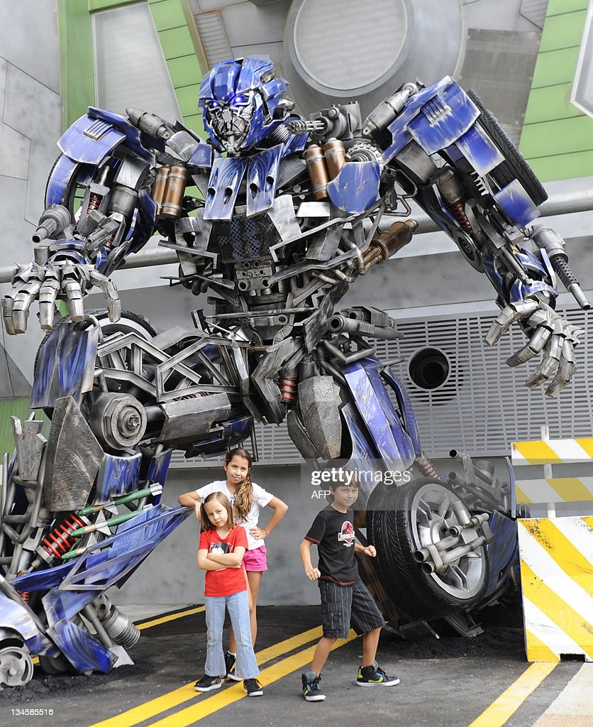 Children pose beside a Transformers robot on the launch day of the new amusement park ride at Universal Studios Singapore on December 3, 2011. 'Transformers: The Ride' is based on the Transformers movie franchise directed by Michael Bay.