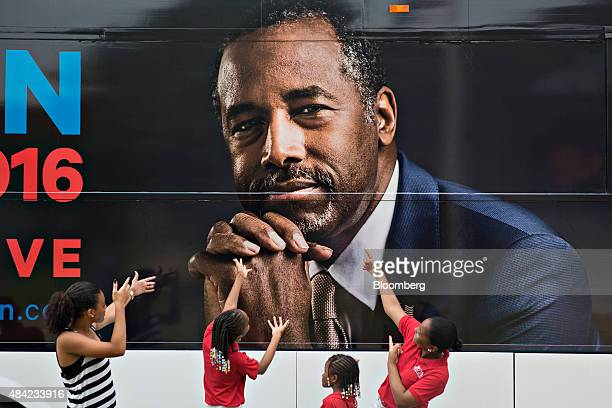 Children pose for a photograph next to the campaign bus of Ben Carson 2016 Republican presidential candidate as it sits outside Maple Street...