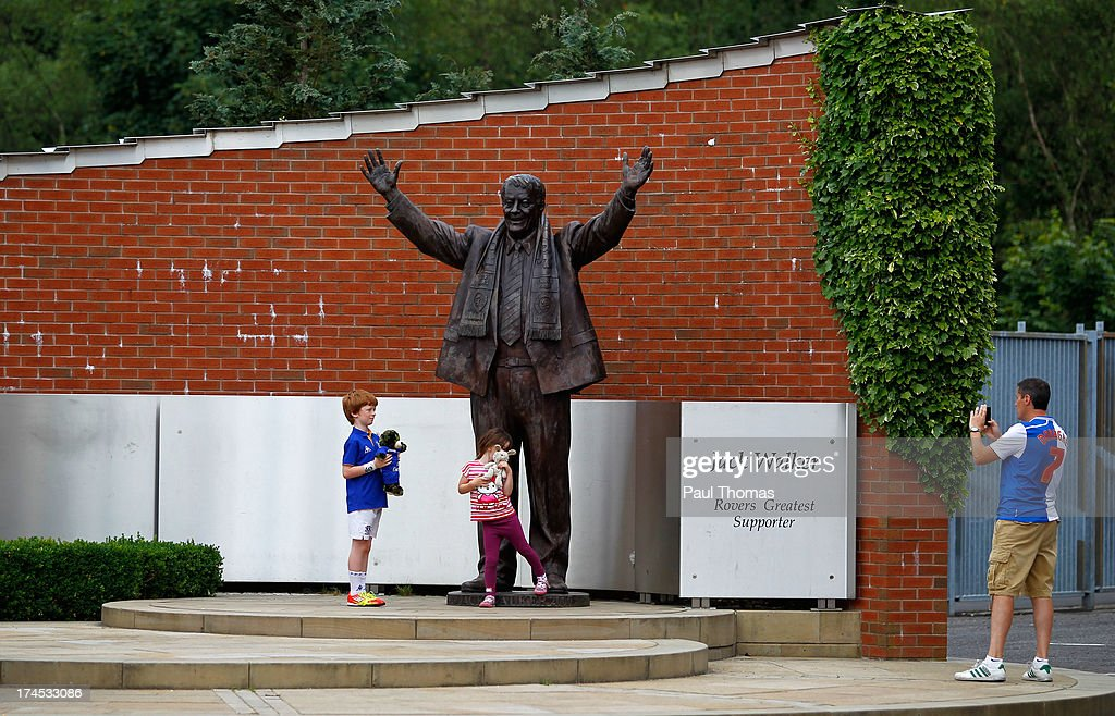 Children pose for a photograph next to the Jack Walker statue before the Pre Season Friendly match between Blackburn Rovers and Everton FC at Ewood Park on July 27, 2013 in Blackburn, England